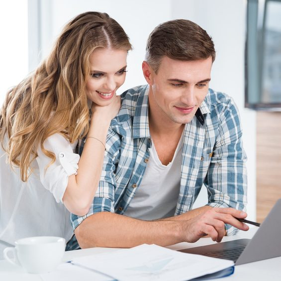 Beautiful couple using laptop and working together at home